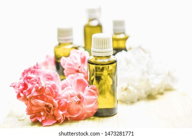 Essential oil bottles are used in spa shops and blurred pink flower
