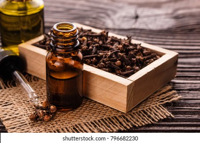 essential oil of cloves on a wooden rustic background.
