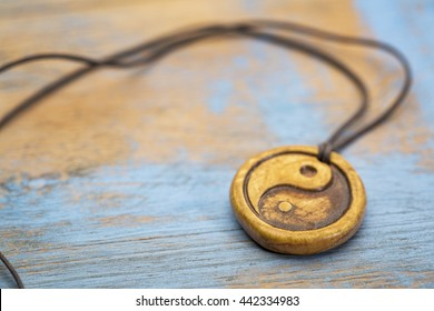 essential oil diffuser ceramic pendant with yin and yang symbol on grunge wood - selective focus