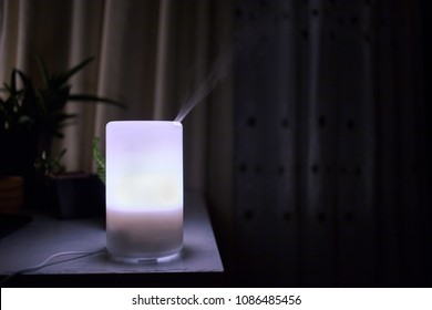 Essential oil diffuser producing mist while glowing in the dark
