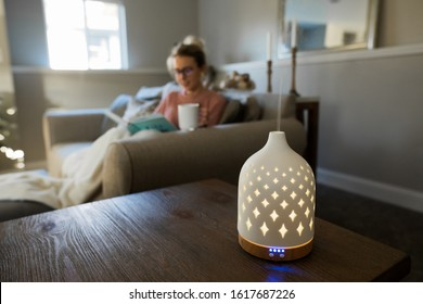 Essential oil diffuser with a young woman relaxing in the background