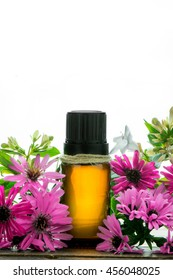 Essential oil, empty tags and small pink flowers, white background