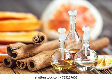 Essential oil in glass bottle with cinnamon sticks and dried red circle slices of citrus fruits orange and lemons on wooden background. Beauty treatment. Spa concept. Selective focus, macro.