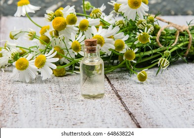 essential oil in glass bottle with fresh chamomile flowers on old table