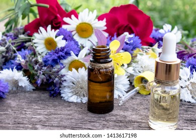 Essential oil in a glass bottle near wildflowers on wooden background. Close-up.