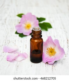 essential oil in glass bottles with dog rose flowers