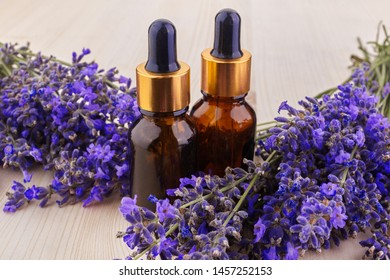 essential oil and lavender flowers on wooden table