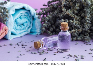 Essential Oil of Lavender on the pastel tone surface with dry lavender flower and bath towels.