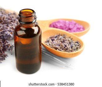 Essential oil, lavender and sea salt on white background
