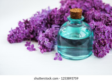 Essential oil with lilac flowers on a white wooden background