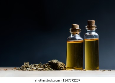 Essential oil made from medicinal cannabis. Buds. detail of Bottle with CBD oil on wood background, Cannabis Oil - medical marijuana concept