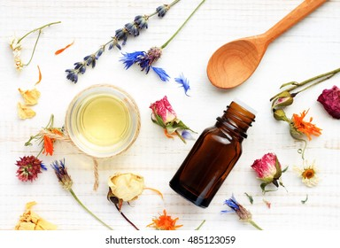 Essential oil, medicinal plant mix, herbal skincare ingredients. Top view Aroma dropper bottle, dried leaves,flowers,herbs, extract sample,spoon.