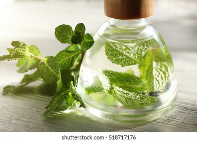 Essential oil with mint on wooden table
