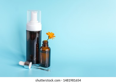 Essential oil in open brown dropper bottle with lying glass pipette, big bottle with white dispenser and orange flower calendula on blue background. Concept natural organic beauty cosmetics product.