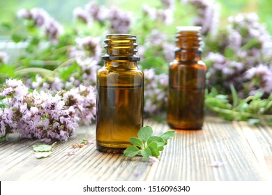 Essential oil of oregano in a bottle and fresh flowers on a wooden table Natural cosmetics and aromatherapy