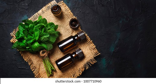 Essential oil of peppermint in a small brown bottle with fresh green mint, black background, top view