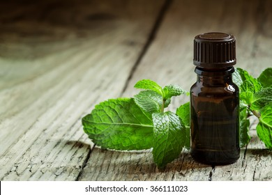 Essential oil of peppermint in a small brown bottle with fresh green mint on an old wooden background, selective focus