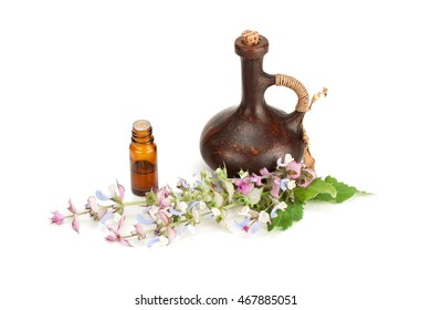 Essential oil of sage and flowers on a white background.