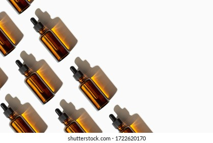 Essential oil or serum glass bottle pattern isolated on white background. Copy space