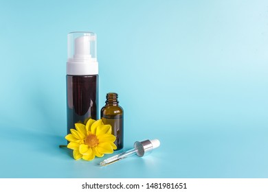 Essential oil in small open brown dropper bottle with lying glass pipette, big bottle with white dispenser and yellow flower on blue background. Concept natural organic beauty cosmetics product.