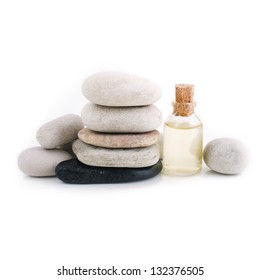 Essential oil and spa stones on a white background