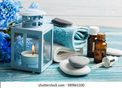 Essential oil spa treatment. Blue flowers, pebbles and candlelight on wooden background.