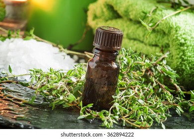 essential oil of thyme in the spa concept with sea salt, towels, burning scented candles, fresh herbs thyme, on a wet dark background, selective focus