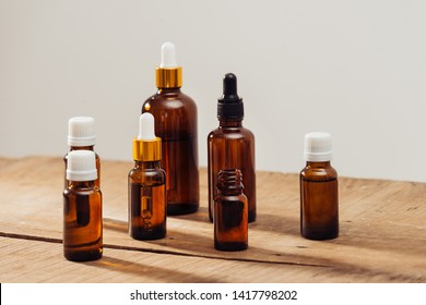 Essential oils bottles on wooden desk with candlelight beside. Spa wellness set.