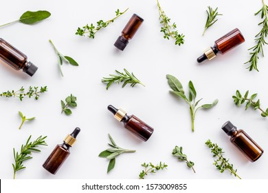Essential oils and fresh herbs on white background top view pattern