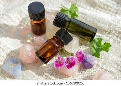 essential oils with geranium flowers on the crystals