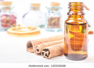 Essential oils in glass bottles and cinnamon on wooden background