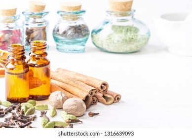 Essential oils in glass bottles maid from spices and nutmeg, cardamon, cinnamon, clove on wooden background