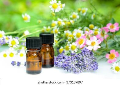 essential oils with herbal flowers in garden