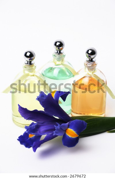 Essential Oils and Iris Flower on White Background.