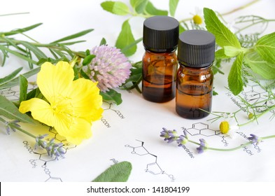 essential oils with medicinal herbs on science sheet