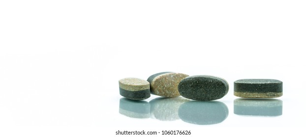 Essential Vitamins and minerals supplements dual layer tablet pills isolated on white background. Multivitamins plus reishi mushroom, wheatgrass, white tea and organic spirulina. Whole food nutrients.