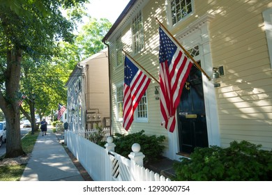 ESSEX, CONNECTICUT, USA - June 19, 2018: American flags and a white picket fence line Main Street in Essex, an all-American village.