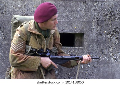 Essex England July 1995. A reenactor dressed in the uniform of a WW2 British Paratrooper standing in front of a concrete bunker holding a Sten machine gun.