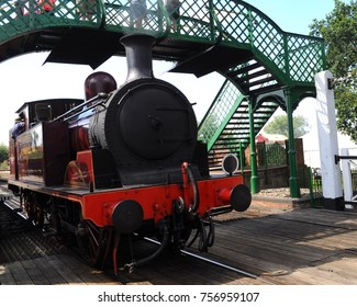 Essex, UK - 08/13/17: 1898 Metropolitan Railway E Class 0-4-4 'Metropolitan Railway No.1' under the Great Eastern Railway Footbridge at North Weald Station of the Epping Ongar Railway.