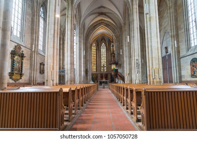 ESSLINGEN GERMANY - SEPTEMBER 13; Long aisle between rows of pews to alter and stained glass windows inside traditional church September 13 2017 Esslingen Germany