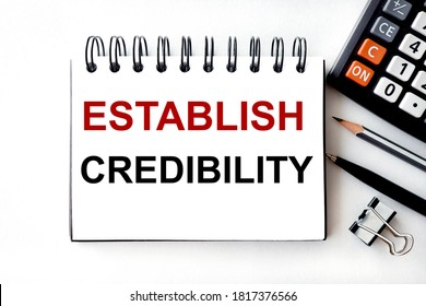 establish credibility. text on notepad pages on white paper on light background near calculator and pen