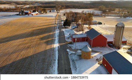 Establishing shot of Midwestern countryside in winter.  Aerial view of  rustic road, farm houses, farms along the street. Agricultural field  covered in first snow, sunny, soft sunlight at sunset
