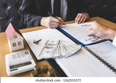 Estate agent broker presenting and wait to client after signing agreement contract real estate with approved application form, buying or concerning mortgage loan offer for and house insurance.
