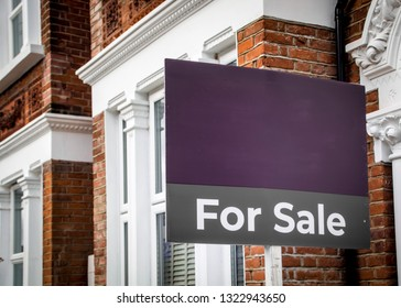 Estate agent 'For Sale' sign board with brick houses in background