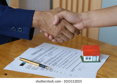 Estate agent giving hand for shaking hands with customers with  house model on wooden desk: real estate, home loan and insurance concept