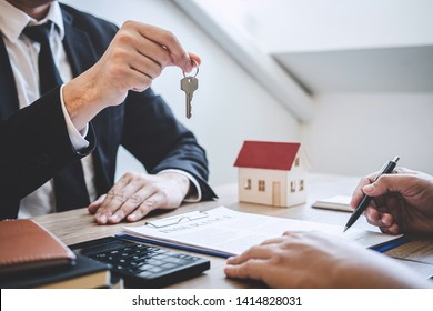 Estate agent giving house keys to client after signing agreement contract real estate with approved mortgage application form, concerning mortgage loan offer for and house insurance.