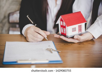 estate agent giving house keys to female and sign agreement in office