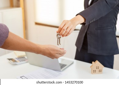 estate agent giving house keys to man and signed agreement in office, estate agent giving keys of new house with customer in office.