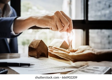 estate agent giving house keys  of customer  and holding dollar us bank at  agency office. agreement concept.