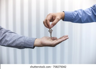 Estate agent giving house keys to man in office